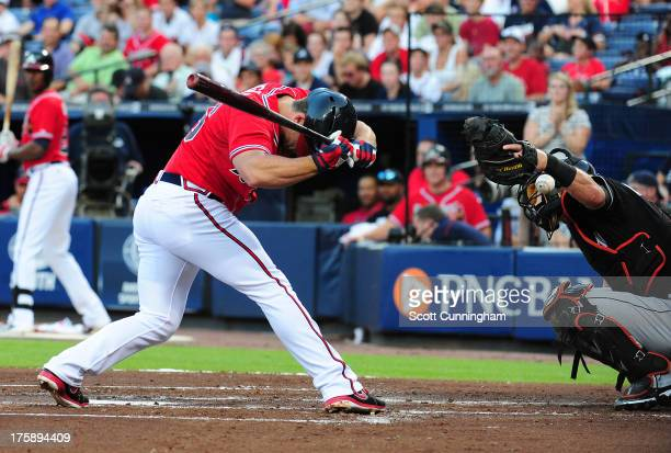 Dan Uggla of the Atlanta Braves is hit by a firstinning pitch thrown by Jacob Turner of the Miami Marlins at Turner Field on August 9 2013 in Atlanta...