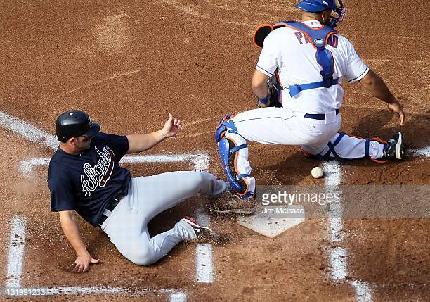 Dan Uggla of the Atlanta Braves scores a run against Ronny Paulino of the New York Mets at Citi Field on September 8 2011 in the Flushing...