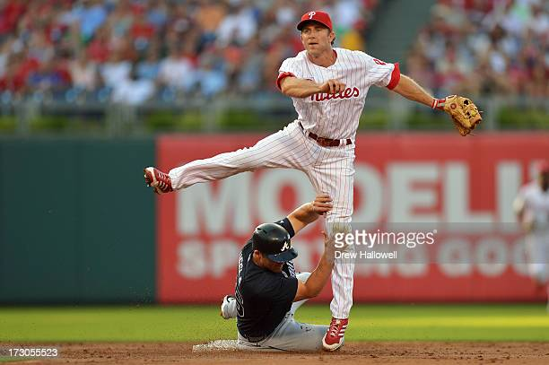 Dan Uggla of the Atlanta Braves slides into Chase Utley of the Philadelphia Phillies on a double play in the second inning at Citizens Bank Park on...