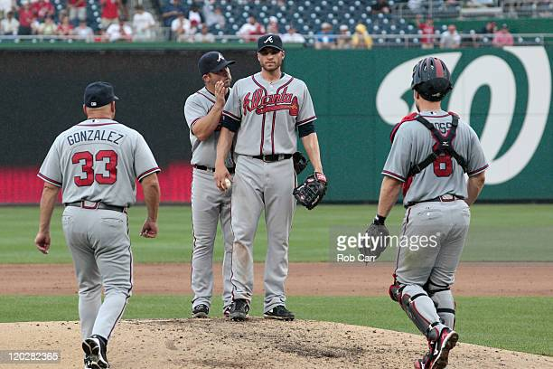 Dan Uggla of the Atlanta Braves talks with starting pitcher Brandon Beachy before being pulled by manager Fredi Gonzalez during the sixth inning...