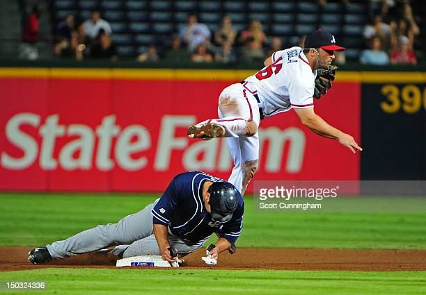 Dan Uggla of the Atlanta Braves turns a double play against Carlos Quentin of the San Diego Padres at Turner Field on August 15 2012 in Atlanta...