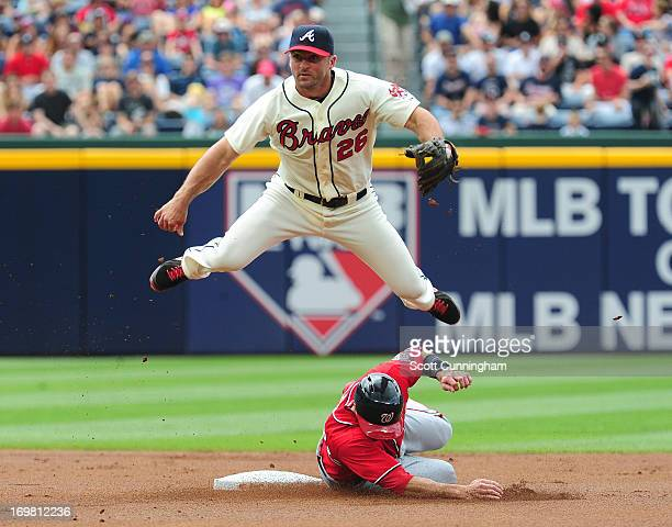 Dan Uggla of the Atlanta Braves turns a double play against Steve Lombardozzi of the Washington Nationals at Turner Field on June 2 2013 in Atlanta...
