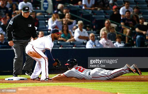Dan Uggla of the Washington Nationals slides safely into third base against Alberto Callaspo of the Atlanta Braves on a 2RBI triple in the seventh...