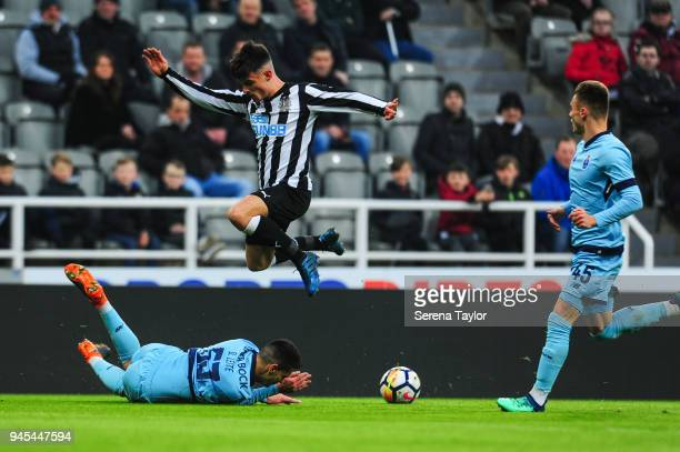 Dan Ward of Newcastle United jumps over a challenging Diogo Leite of FC Porto during the Premier League International Cup match between Newcastle...