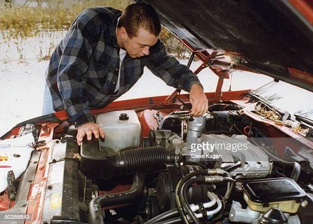 Dan Weber who was disowned by parents Ken Diane working on engine of his car outside