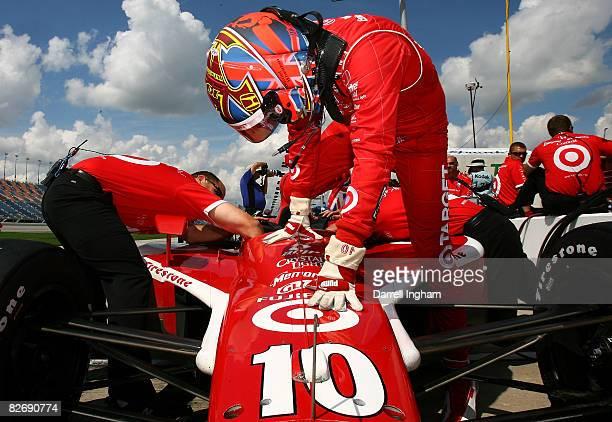 Dan Wheldon climbs aboard the Target Chip Ganassi Racing Dallara Honda during practice for the IRL IndyCar Series PEAK Antifreeze Motor Oil Indy 300...
