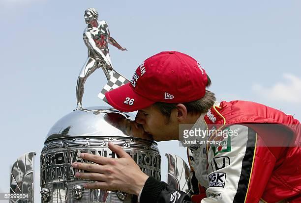 Dan Wheldon driver of the Andretti Green Racing Jim Beam Klein Tools Dallara Honda kisses the BorgWarner Trophy on the Yard of Bricks a day after...