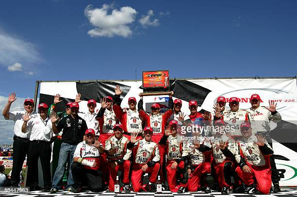 Dan Wheldon driver of the Andretti Green Racing Klein Tools/Jim Beam Dallara Honda celebrates his fifth victory with his crew after winning the Indy...