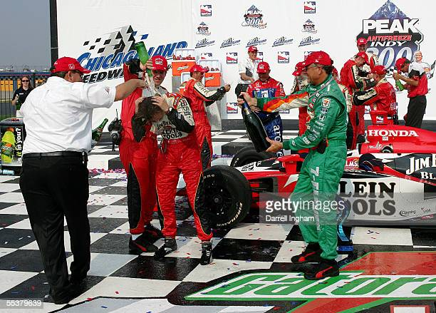 Dan Wheldon driver of the Andretti Green Racing Klein Tools/Jim Beam Dallara Honda is showered with champagne from team owners Kim Green and Kevin...