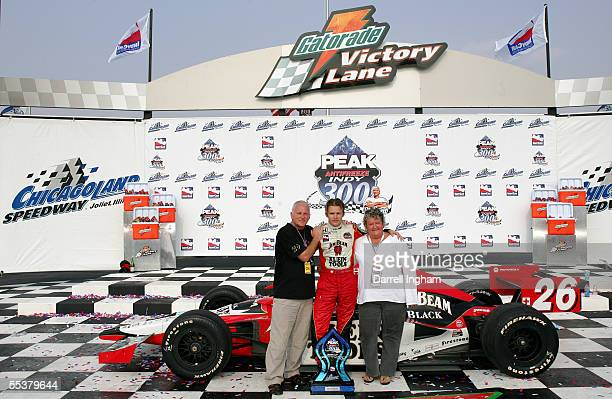 Dan Wheldon driver of the Andretti Green Racing Klein Tools/Jim Beam Dallara Honda poses with his father Clive and mother Sue after winning the Indy...