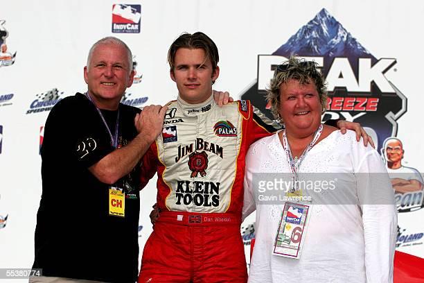 Dan Wheldon driver of the Klein Tools/Jim Beam Andretti Green Racing Jim Dallara Honda poses with his parents Clive and Sue on the winner's podium...