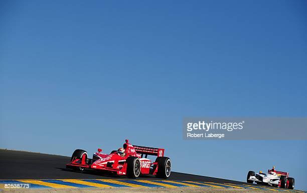 Dan Wheldon driver of the Target Chip Ganassi Racing Dallara Honda leads Mario Dominguez during the IndyCar Series PEAK Antifreeze Motor Oil Indy...