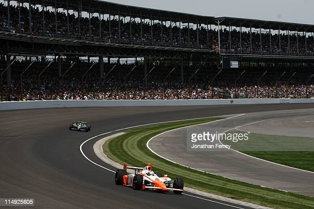 Dan Wheldon of England driver of the William RastCurb/Big Machine Dallara Honda races during the IZOD IndyCar Series Indianapolis 500 Mile Race at...