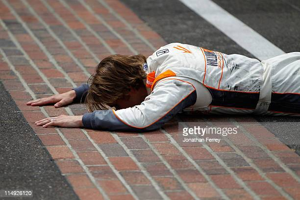 Dan Wheldon of England driver of the William RastCurb/Big Machine Dallara Honda kisses the bricks at the start/finish line after winning the IZOD...