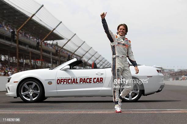 Dan Wheldon of England driver of the William RastCurb/Big Machine Dallara Honda celebrates at the start/finish line after winning the IZOD IndyCar...