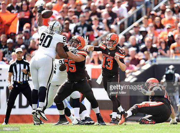 Dan Williams of the Oakland Raiders blocks a pass by Josh McCown in front of Alex Mack of the Cleveland Browns during the first quarter at...