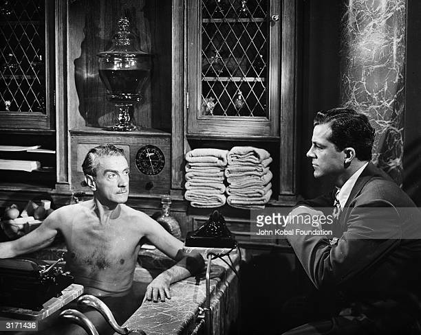 Dana Andrews in the role of Detective McPherson questions Waldo Lydecker in his luxurious marble bath in the film 'Laura' directed by Otto Preminger