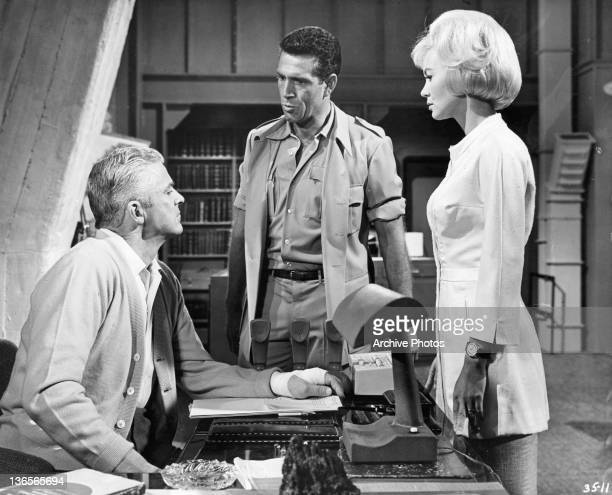 Dana Andrews is addressed by Kieron Moore and Janette Scott in a scene from the film 'Crack In The World' 1965