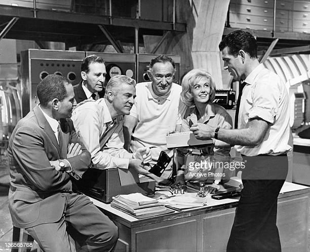 Dana Andrews Janette Scott and other scientists look at Kieron Moore in a scene from the film 'Crack In The World' 1965