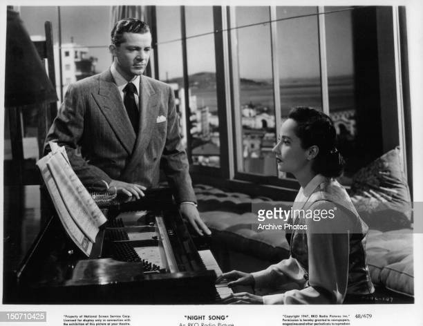 Dana Andrews watching Merle Oberon at the piano in a scene from the film 'Night Song' 1947