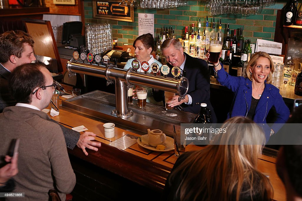 Dana Bash holds up a fresh poured beer as Senator Lindsey Graham and his sister Darline Graham Nordone serve guests priot to CNN's Politics On Tap at Walnut Brewery on October 27, 2015 in Boulder, Colorado. 25763_001