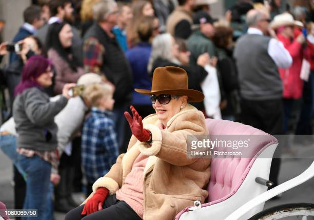 Dana Crawford this year's grand marshall of the parade waves to the crowds from her carriage during the annual National Western Stock Show parade as...