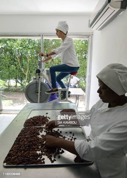 Dana Mroueh owner of the handmade organic raw chocolate factory Mon Choco uses a bicycle to grind cocoa beans as one of her employees sorts them at...