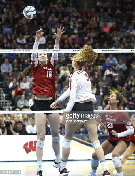 Dana Rettke of the Wisconsin Badgers blocks an attack by Holly Campbell of the Stanford Cardinal during the NCAA Division 1 Championship game at PPG...