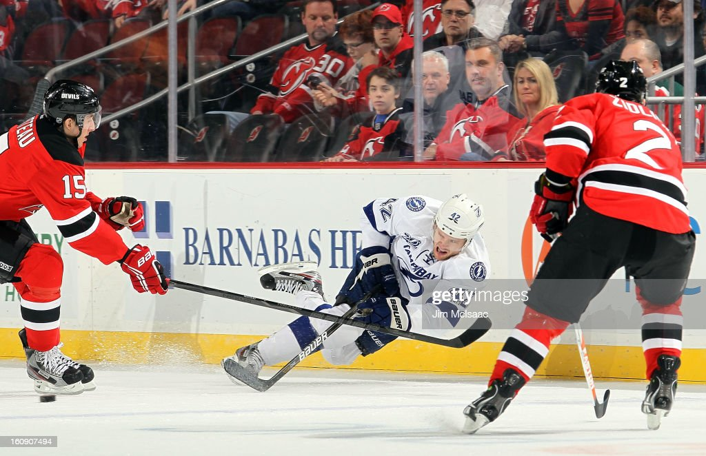 Dana Tyrell #42 of the Tampa Bay Lightning plays the puck in the first period against Stefan Matteau #15 and Marek Zidlicky #2 of the New Jersey Devils at the Prudential Center on February 7, 2013 in Newark, New Jersey.