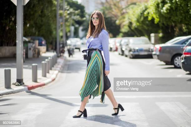 Dana Zarmon wearing blue white striped button shirt Alexander Wang Stradivarius skirt with slit Chloe belt bag Prada shoes sunglasses seen during Tel...