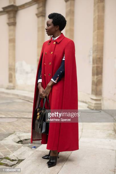 Danai Gurira is seen on the street attending THOM BROWNE during Paris Fashion Week AW19 wearing THOM BROWNE red coat and black bag on March 03, 2019...