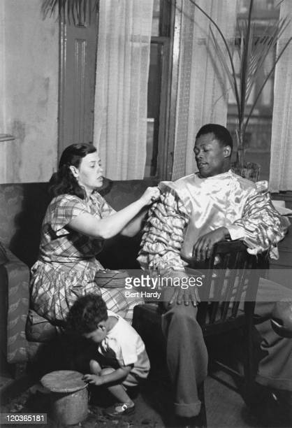 Dance band leader Herman McKay, who performs as Alfonso Perez, at home with his wife and child in Britain, 1949. Original Publication : Picture Post...