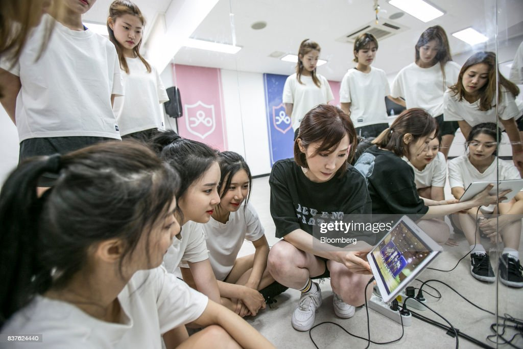 A dance instructor, center, and contestants watch a video during a dance practice session during the production of the 'Idol School' reality television show by CJ E&M Corp. at the Yangpyeong English School in Yangpyeong, South Korea, on Thursday, June 29, 2017. Endless repetition, tear-inducing critiques from coaches, smile practice, and psychological counselling are plot points in an 11-week reality TV show documenting the creation of a teeny-bopper singing group. Idol School, which began airing in July, is part of a corporate push to turn Korean pop music into a global phenomenon. Photographer: Jean Chung/Bloomber