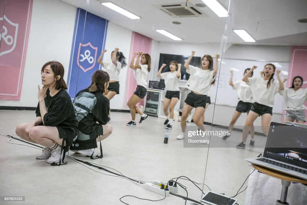 A dance instructor, left, watches as contestants practice dance moves during the production of the 'Idol School' reality television show by CJ E&M Corp. at the Yangpyeong English School in Yangpyeong, South Korea, on Thursday, June 29, 2017. Endless repetition, tear-inducing critiques from coaches, smile practice, and psychological counselling are plot points in an 11-week reality TV show documenting the creation of a teeny-bopper singing group. Idol School, which began airing in July, is part of a corporate push to turn Korean pop music into a global phenomenon. Photographer: Jean Chung/Bloomber