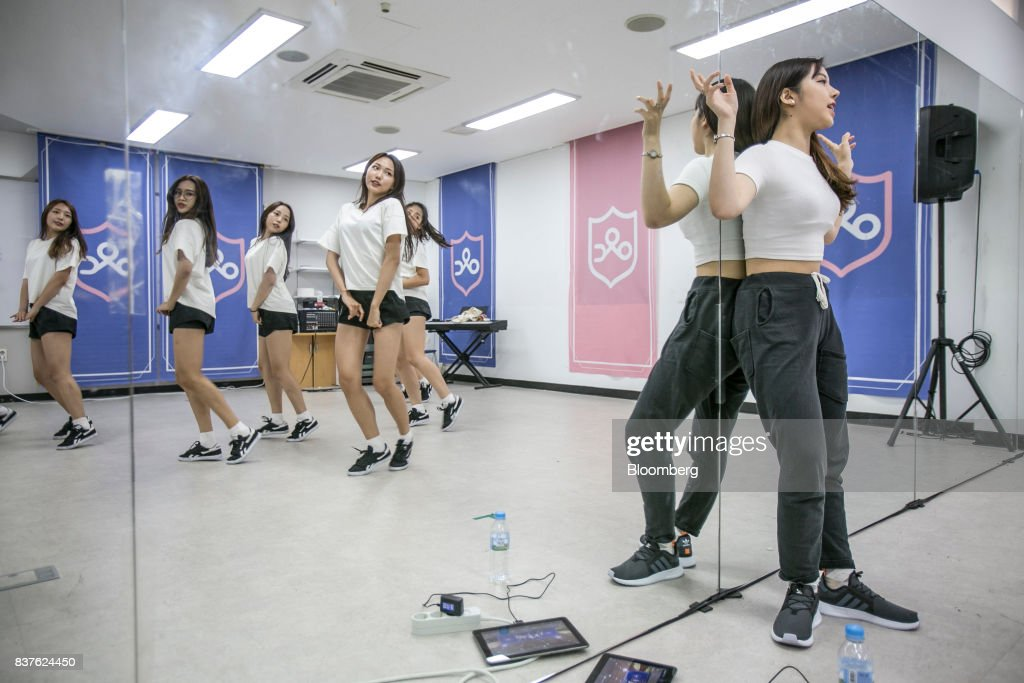 A dance instructor, right, watches as contestants practice dance moves during the production of the 'Idol School' reality television show by CJ E&M Corp. at the Yangpyeong English School in Yangpyeong, South Korea, on Thursday, June 29, 2017. Endless repetition, tear-inducing critiques from coaches, smile practice, and psychological counselling are plot points in an 11-week reality TV show documenting the creation of a teeny-bopper singing group. Idol School, which began airing in July, is part of a corporate push to turn Korean pop music into a global phenomenon. Photographer: Jean Chung/Bloomber