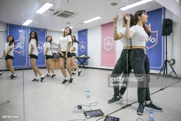 A dance instructor right watches as contestants practice dance moves during the production of the 'Idol School' reality television show by CJ EM...