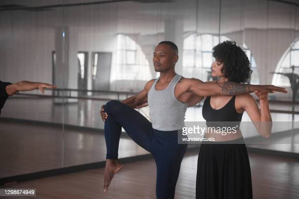 dance instructor teaching student helping with form in studio - teacher stock pictures, royalty-free photos & images