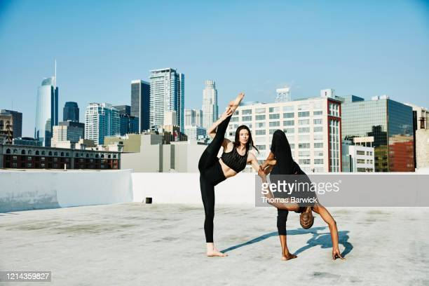dance partners balancing on each other while performing on rooftop overlooking city - friendly match stockfoto's en -beelden