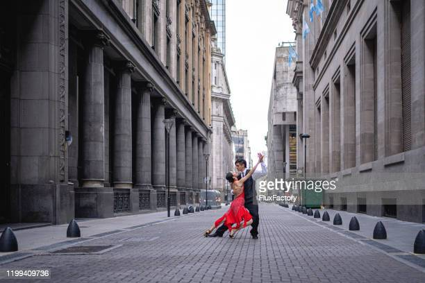 dance partners performing tango argentino in an old street - argentina stock pictures, royalty-free photos & images