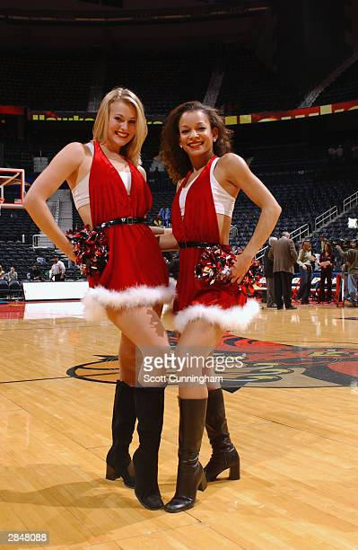 Dance Team members Brandy and Jessica of the Atlanta Hawks pose in their Christmas Santa Claus outfits before the game against the Boston Celtics on...