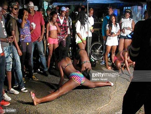Dancehall reggae enthusiasts crowd a parking lot in a West Kingston neighborhood turning it into an Xrated street party that is live streamed over...