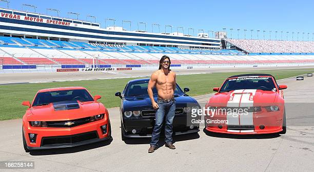 Dancer Alex Biffin from the show 'Thunder Down Under' poses in front of Chevrolet Camero ZL1 Dodge Challenger SRT8 392 and a Ford Mustang Shelby...