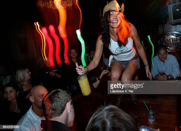 Dancer Amy Tzagournis on a table dancing during Coyote Ugly night at Patrick Molloy's an old–fashioned singles bar in Hermosa Beach