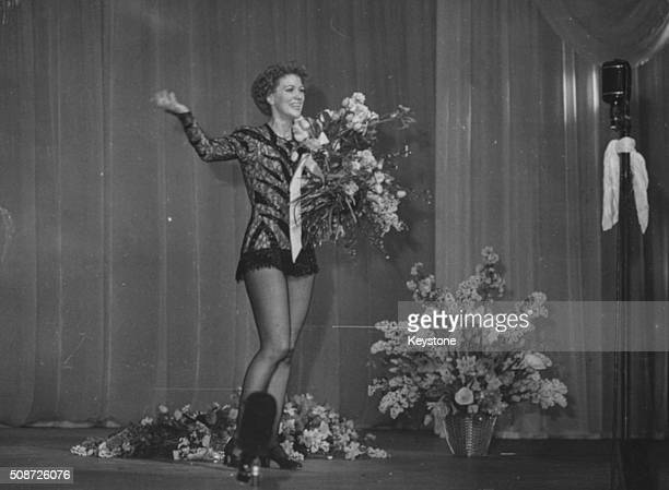 Dancer and actress Eleanor Powell holding a bouquet of flowers following a performance on the stage March 21st 1949