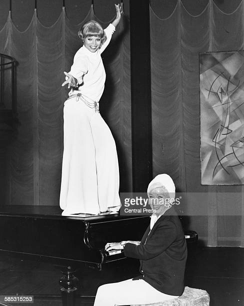 Dancer and performer Ginger Rogers playing the piano as Juliet Prowse dances during rehearsals for the show 'Mame' at the Theatre Royal on Drury Lane...