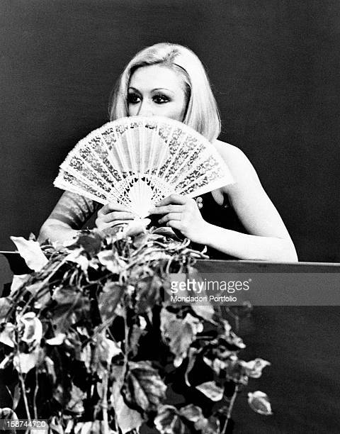 Dancer and presenter Raffaella Carrà in a dress showing her shoulders and a fan covering part of her face during the rehearsal of the TV show...