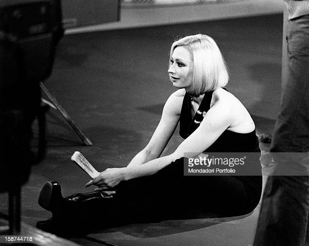 Dancer and presenter Raffaella Carrà sitting on the floor in a dress showing her shoulders holding a fan during the rehearsal of the the TV show...