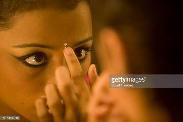 Dancer Ashwini Iyer applies her makeup by applying a bindi to her forehead in a dressing room during a production of The Merchants of Bollywood in a...