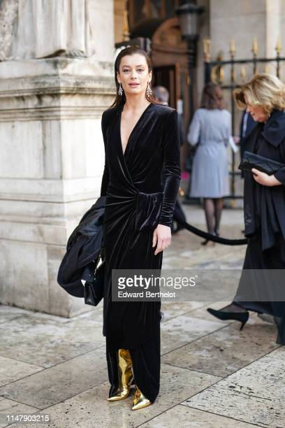 Dancer Aurelie Dupont wears a black velvet dress, golden shiny boots, earrings, outside the Opera Garnier 350th Anniversary Gala in Paris on May 08,...