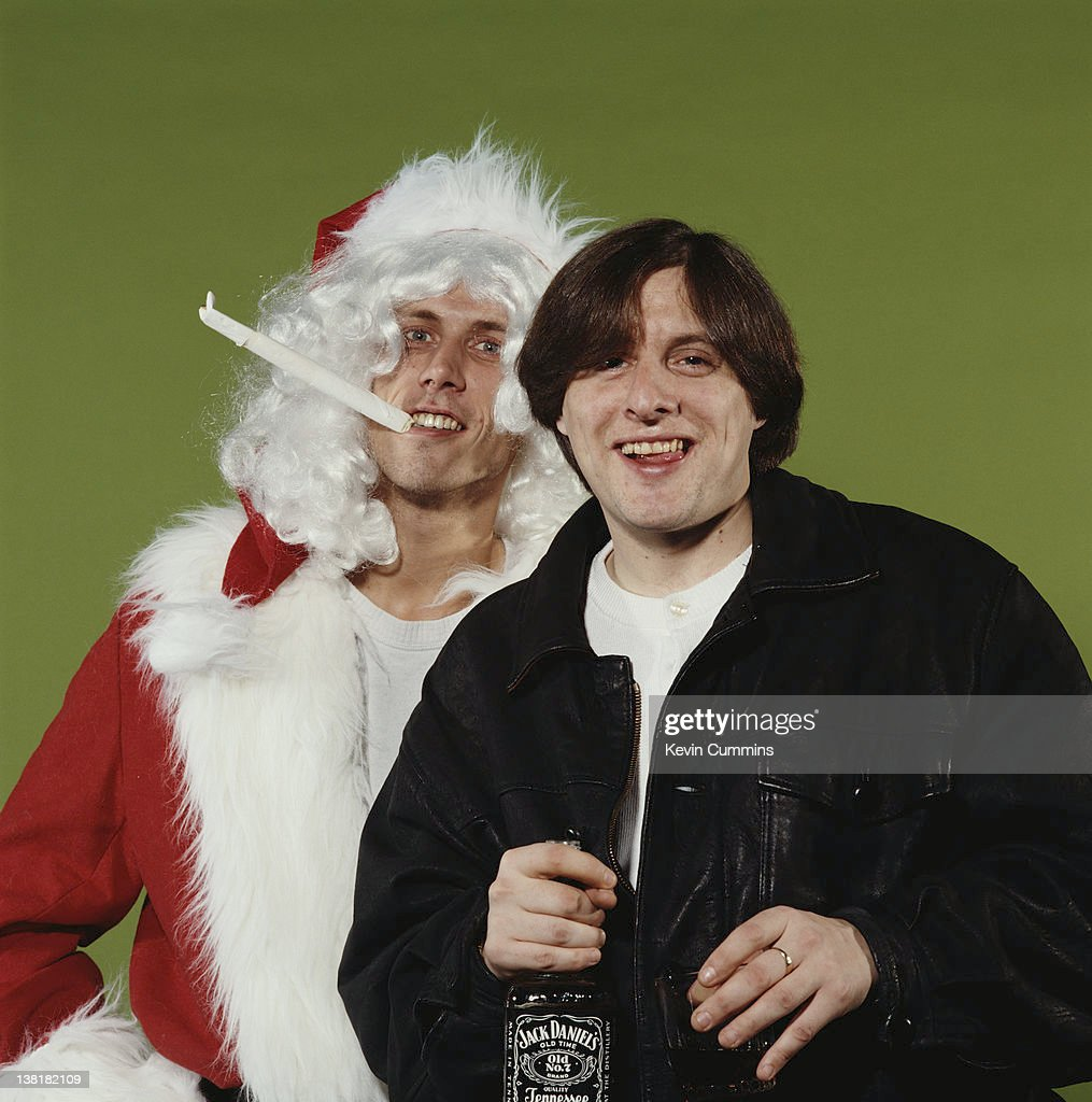 Dancer Bez (left), as a joint-smoking Santa, and singer Shaun Ryder of the Happy Mondays, circa 1990. (Photo by Kevin Cummins/Getty Images) of
